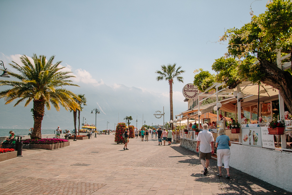 Walking along the promenade lined with restaurants on one side and the lake on the other in Limone, Lake Garda
